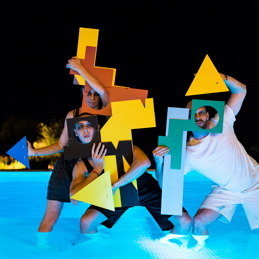 Three performer stand knee-deep in a pool, holding various shapes in front of their faces.