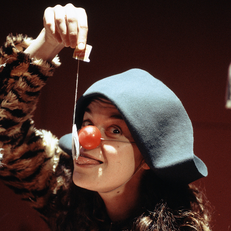 Emmanuelle Delpech performs while wearing a red clown nose.