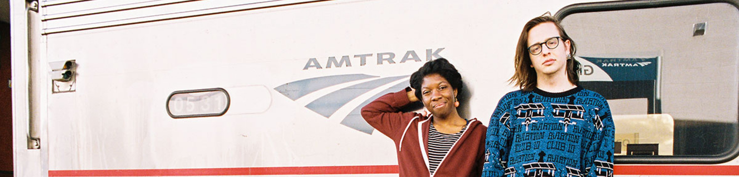 Two students pose in front of the Amtrak.